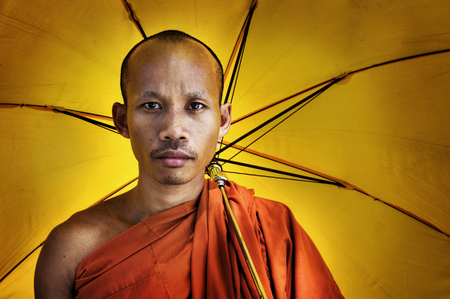 religious clothing: Buddhist monk holding umbrella Ceremony Concept Stock Photo