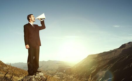 stating: Businessman Shouting on the Top of the Mountain Concept Stock Photo