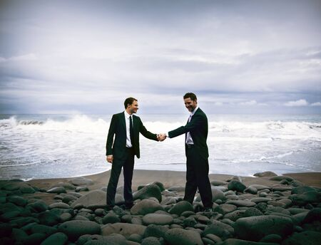 businessmen shaking hands: Businessmen shaking hands with stormy ocean background. Stock Photo