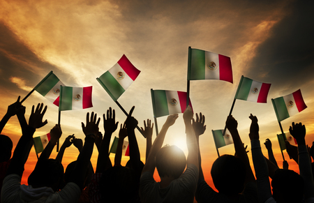 gente saludando: Group of People Waving Mexican Flags in Back Lit