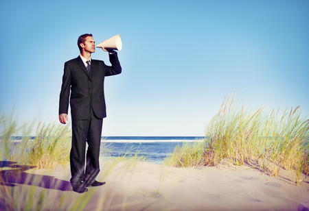 inductive: Business Man Holding loudspeaker on Beach Concept Stock Photo