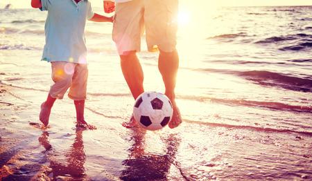 padre e hijo: Padre Hijo que juega a fútbol Concepto de playa del verano