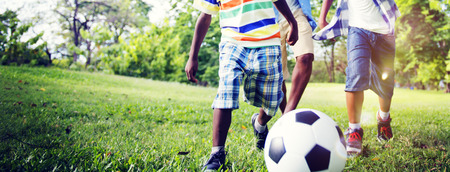 african children: African Brother Playing Football Outdoors Concept Stock Photo