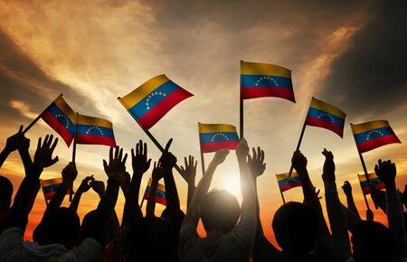 personas saludando: El grupo de personas que agitan de Venezuela en Contraluz