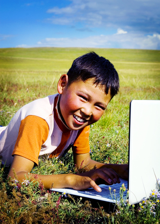 independent mongolia: Mongolian Boy Laptop Grass Technology Connection Concept