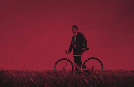 man pushing: Business Man Pushing Bike Outdoors Concept Stock Photo