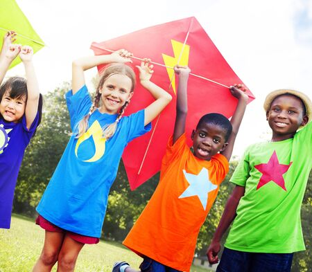 kids playing: Children Flying Kite Playful Friendship Concept Stock Photo