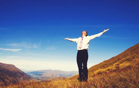 respiraci�n: El hombre de negocios de pie en el concepto de las monta�as