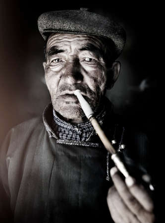 independent mongolia: Mongolian Man in Traditional Dress Smoking a Pipe Concept Stock Photo