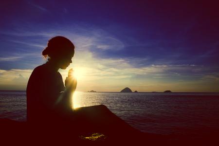 mujer orando: Mujer joven que ruega puesta de sol sobre el océano concepto Foto de archivo