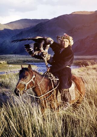 independent mongolia: Kazakh on Horse With Eagle Catching Concept Stock Photo