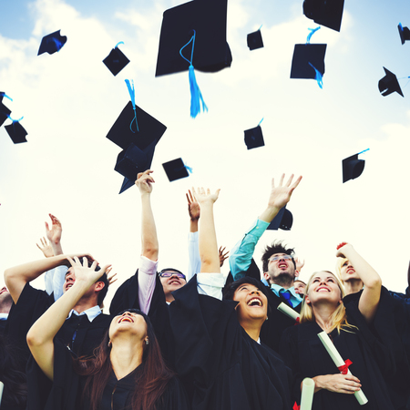 cap and gown: Graduation Caps Thrown Happiness Success Cocnept Stock Photo