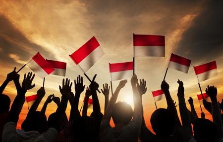 インドネシアの旗を持っている人のシルエット 写真素材