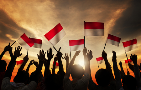 indonesia culture: Silhouettes of People Holding the Flag of Indonesia Stock Photo