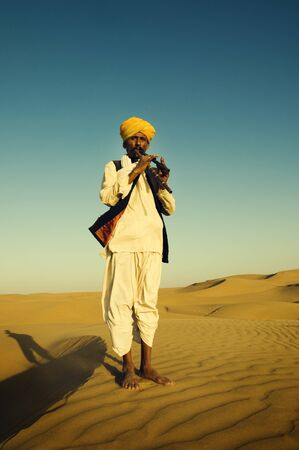 indigenous: Indigenous Indian Man Playing Wind Pipe In A Desert Concept Stock Photo
