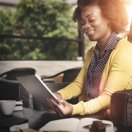 mujeres trabajando: Mujer africana que usa la tablilla Concepto Relajación Foto de archivo
