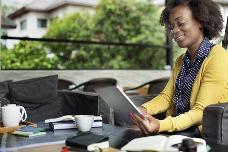 mujer pensando: Mujer africana que usa la tablilla Concepto Relajaci�n Foto de archivo