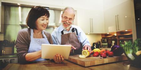 marido y mujer: La esposa del marido Cocinar la b�squeda Men� Tablet Concept Foto de archivo