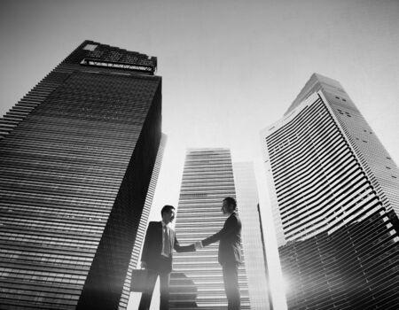 mixed age: Businessmen Cityscape Handshake Partnership Concept Stock Photo