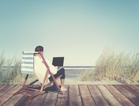 away from it all: Businessman Working by the Beach Relaxation Concept