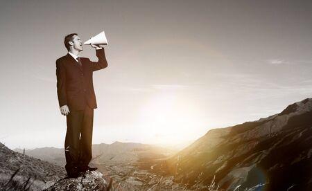 stating: Businessman Shouting Mountain Announcement Speech Concept