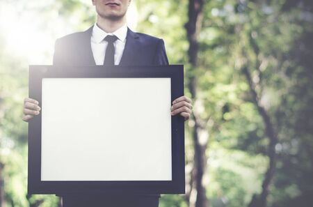 man holding sign: Businessman Holding Picture Frame Copy Space Concept Stock Photo