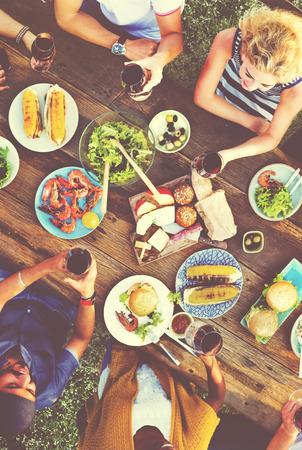 juntos: Pessoas ocasional que come junto ao ar livre Concept