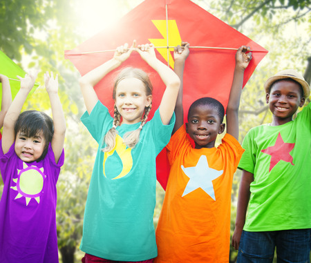 playful: Children Flying Kite Playful Friendship Concept Stock Photo