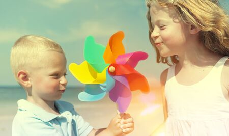 multi age: Brother Sister Blowing Windmill Beach Enjoyment Concept