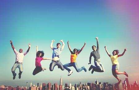 manos levantadas al cielo: Gente alegre que salta Amistad Felicidad City Concepto Foto de archivo
