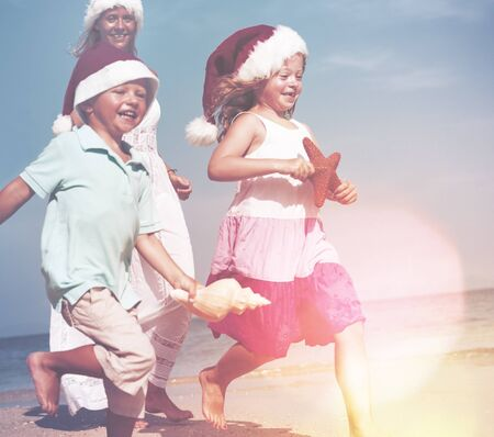getting away from it all: Family Christmas Beach Summer Playing Happiness Concept