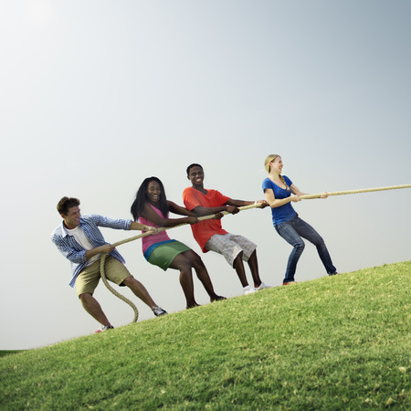 active adult community: Group Casual People Playing Tug War Concept Stock Photo