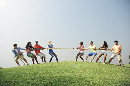Gruppo casuale gente che gioca al tiro alla fune Concetto Archivio Fotografico - 52314051
