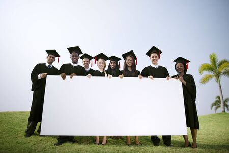 Group Graduating Students Outdoors Holding Placard Concept Stock Photo