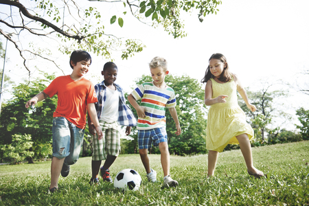 kid  playing: Kids Children Playing Football Fun Happiness Concept Stock Photo