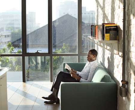 reading magazine: Businessman Reading Magazine Relaxation Concept