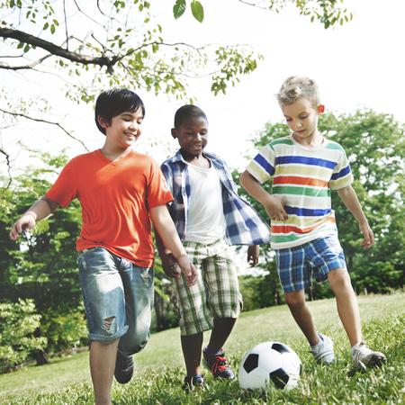 petit bonhomme: Enfants Enfants jouant au football Bonheur Divertissement Concept Banque d'images
