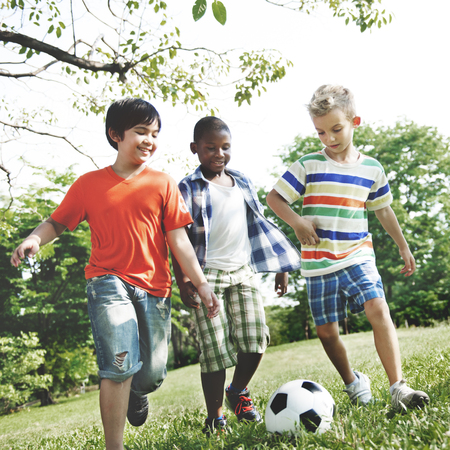 little boys: Kids Children Playing Football Fun Happiness Concept Stock Photo