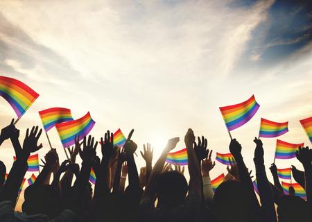 同性恋彩虹旗子人群庆祝武器举起了概念