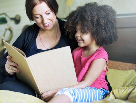 niños sentados: Familia Hijos del libro de lectura Concepto Dormitorio Foto de archivo