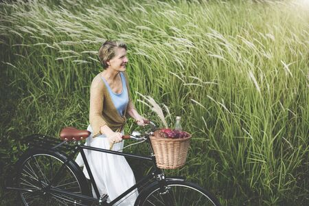 windy: Senior Woman Bicycling Windy Park Concept