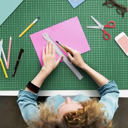workstation: Woman Cutting Paper Stationery Workstation Concept