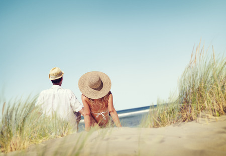 comfort: Couple Sitting Comfortable Beach Grass Holiday Concept