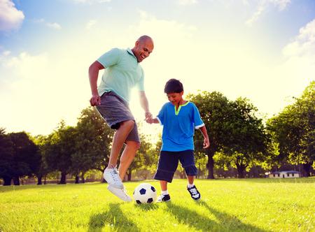 niños jugando: Padre Hijo Jugar Soccer Park Concepto verano Foto de archivo