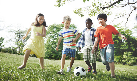 kids football: Kids Children Playing Football Fun Happiness Concept Stock Photo