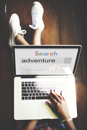 Woman using a laptop with internet search of adventure Banco de Imagens