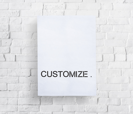 Paper with the word CUSTOMIZE on brick wall