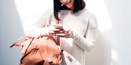 lady on phone: Asian Lady Checking Phone Bag Wall Concept