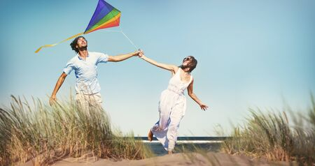 man flying: Cheerful Couple Playing Kite by the Beach Concept