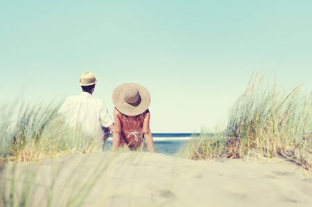 comfortable: Couple Sitting Comfortable Beach Grass Holiday Concept